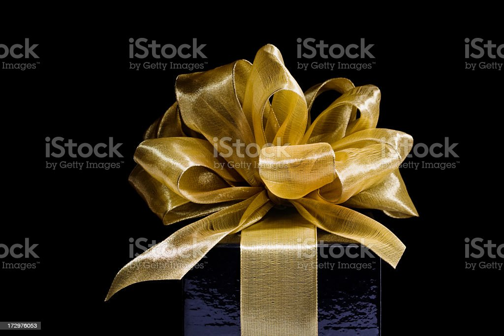 Christmas Gift Wrapped in Gold Ribbons, Bows on Black Background stock photo
