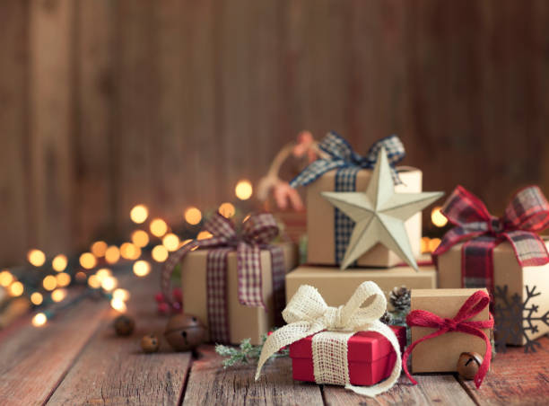 christmas gifts against a wooden background - regalo natale foto e immagini stock