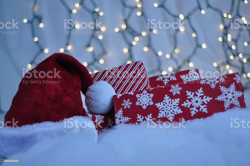 Christmas gifts and Santa hat with lights in background stock photo