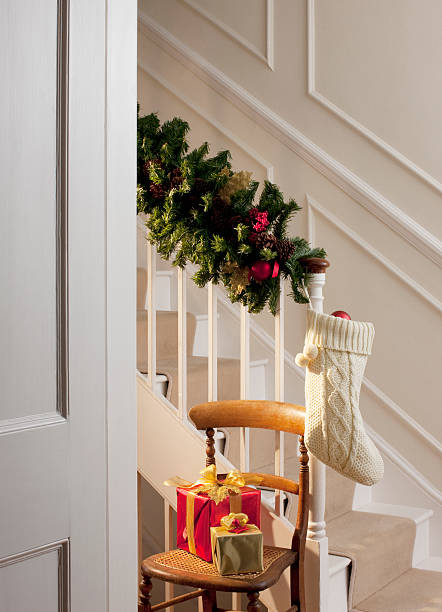 christmas gifts and stocking near staircase - christmas tree stockfoto's en -beelden