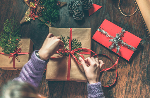 Young woman wrapping Christmas gifts on wooden table