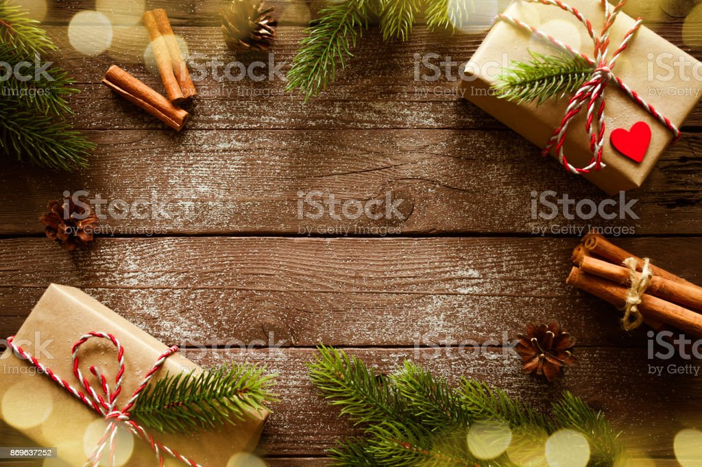 Christmas gifts boxes with fir branches on wooden background top view stock photo