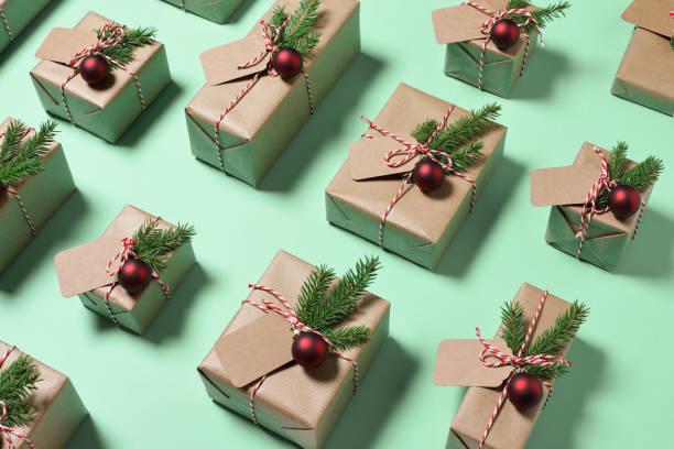 weihnachtsgeschenke geschenke verpackt in rustikalen papier auf grünem hintergrund - weihnachtsideen stock-fotos und bilder