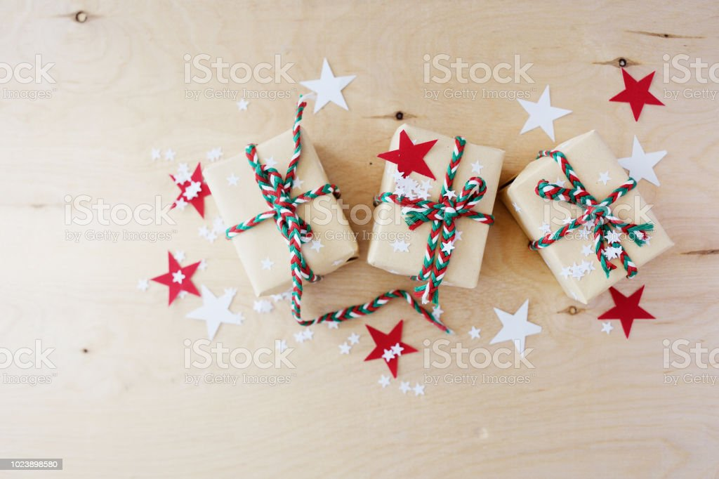 Christmas gifts in kraft to packing on a wooden background stock