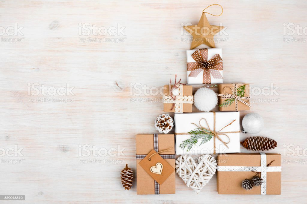 Christmas gifts in shape of fir tree on wooden background stock