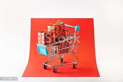 Christmas gifts in shopping cart on red and grey background. Christmas E-commerce concept