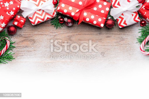 istock Christmas gifts on wooden background table with snow and baubles 1056082590