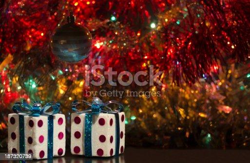Decoración Navideña, mucho color y dos regalos con una esfera colgando.