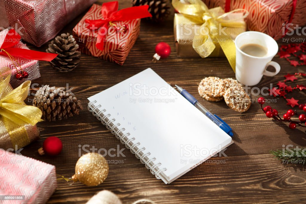christmas gifts presents wish list and christmas decorations on wood background christmas lifestyle concept