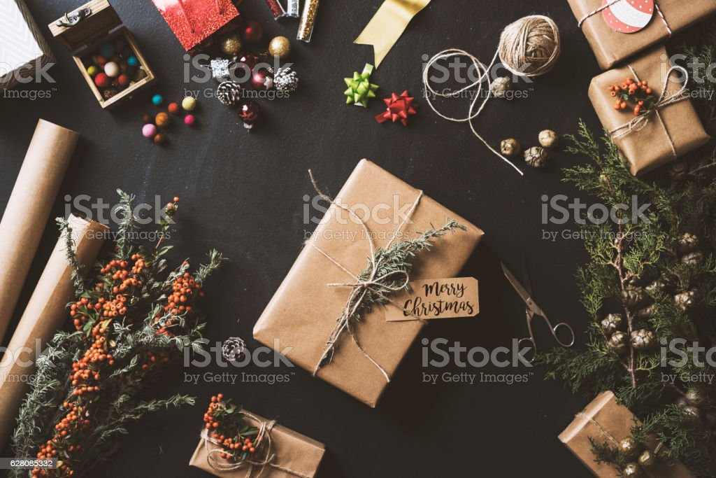 Christmas gifts, table top flat lay Christmas concept table top flat lay on blackboard. Gift box with a card on table. Wrapping paper, jute string, gift box, Christmas ornament, pine cones and firethorn branches on blackboard background. Backgrounds Stock Photo