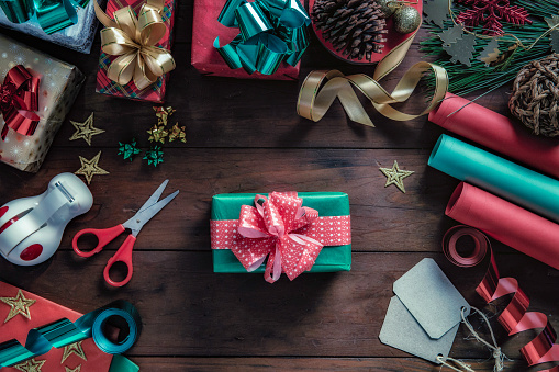 Christmas Gifts wrapping accessories on a rustic table. Christmas themes.