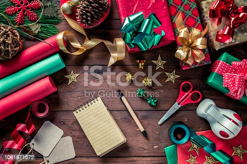 Christmas gifts wrapping on rustic table with note pad for wish list. Christmas themes.