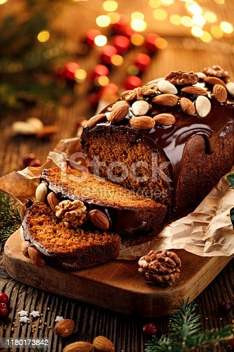 istock Christmas gingerbread cake covered with chocolate and decorated with nuts and almonds on the holiday table, close-up. 1180173842