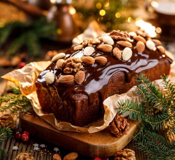 weihnachts-lebkuchen, lebkuchen mit schokolade bedeckt und mit nüssen und mandeln auf dem festtisch verziert. - schokoladen biskuitkuchen stock-fotos und bilder