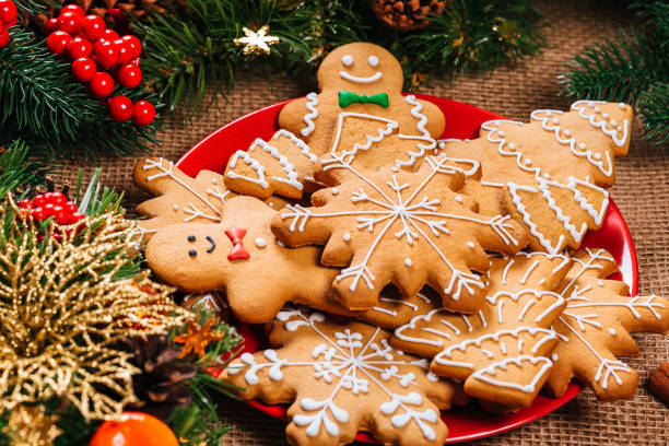 christmas gingerbread cookies homemade in red plate with branches of christmas tree and new year decor on table with burlap tablecloth. merry christmas postcard. - christmas cookies imagens e fotografias de stock