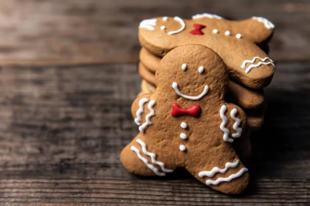 galletas de pan de jengibre de navidad sobre mesa de madera - gingerbread man fotografías e imágenes de stock