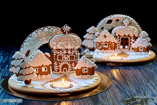 Christmas gingerbread house with a burning candle on a dark wooden surface against a black background.