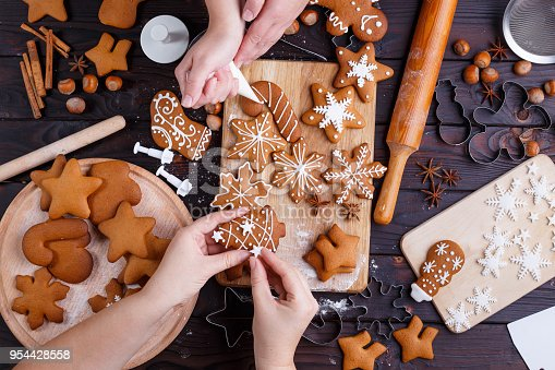 istock Christmas gingerbread making. Friends decorating freshly baked c 954428558