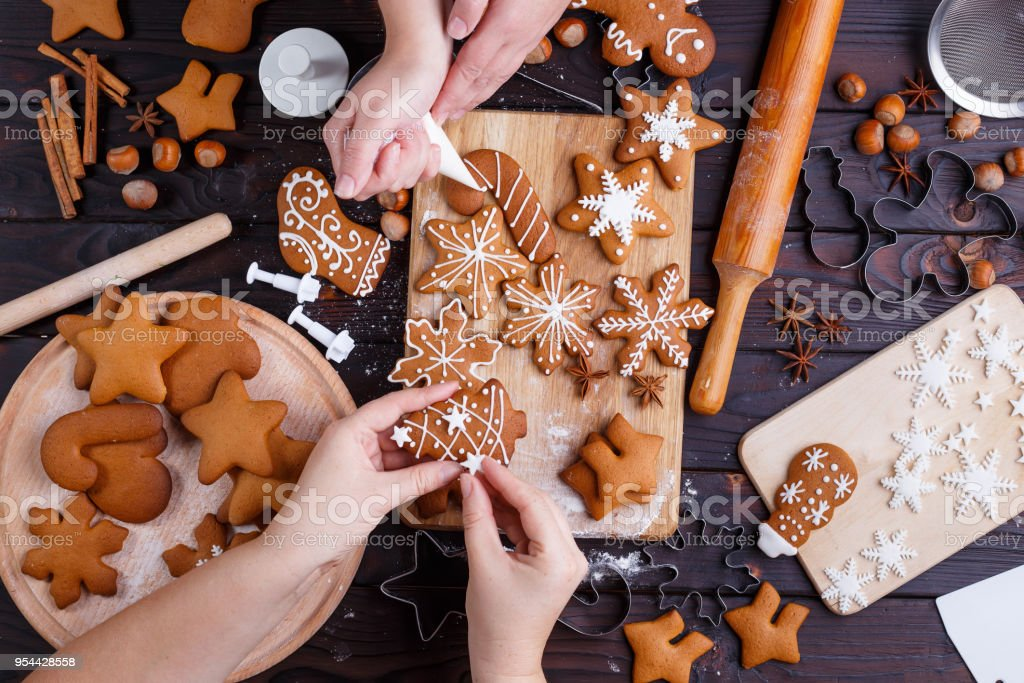 Christmas gingerbread making. Friends decorating freshly baked c stock photo