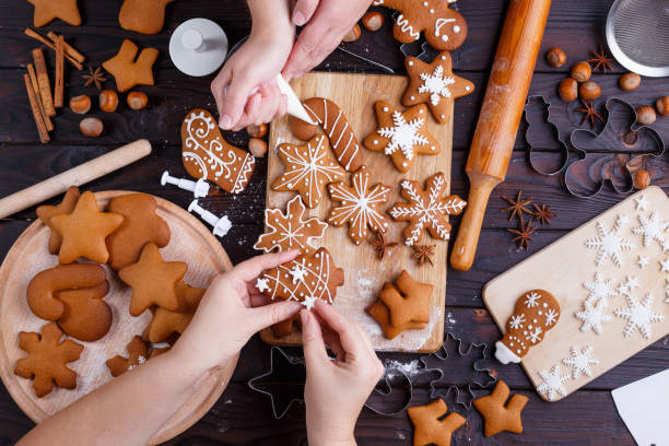 christmas gingerbread making. friends decorating freshly baked c - christmas cookies stock pictures, royalty-free photos & images