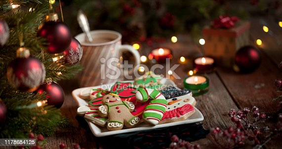 1059144984 istock photo Christmas gingerbread man, cookies and hot chocolate on an old wood background 1178684125