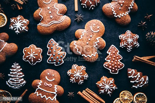 Directly above shot of decorated gingerbread cookies with spices on table. Homemade Christmas cookies on gray background.