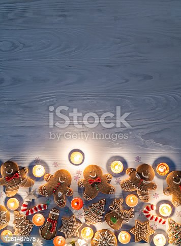 Christmas gingerbread man cookies, snowman, stars, snowflake, candy cane, reindeer and fir trees with candle lights on rustic wooden white background with copy space