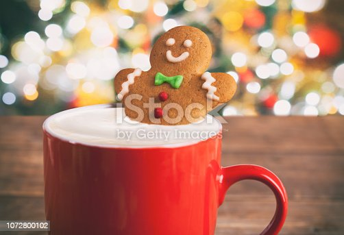 Christmas gingerbread man in hot chocolate on rustic wooden table.