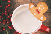 Christmas gingerbread man in hot chocolate on rustic wooden table. The font used is free for commercial use.