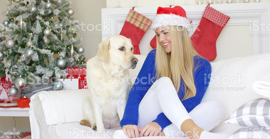 Christmas girl with her dog friend at the couch foto royalty-free