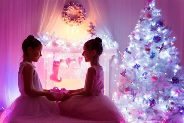 weihnachten mädchen, glückliche kinder präsent geschenk, beleuchtung dekorierten weihnachtsbaum - lila mädchen zimmer stock-fotos und bilder