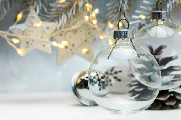 christmas glass balls hanging against grey background with blurred garland lights stock photo