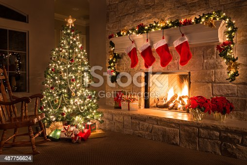 Glowing Christmas fireplace and living room, with tree, and stockings hanging from mantel by fireplace.Waiting for Santa.