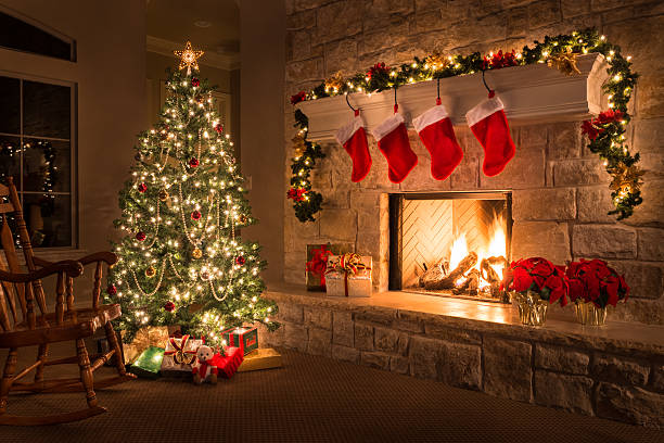 christmas. glowing fireplace, hearth, tree. red stockings. gifts and decorations. - fireplace stockfoto's en -beelden