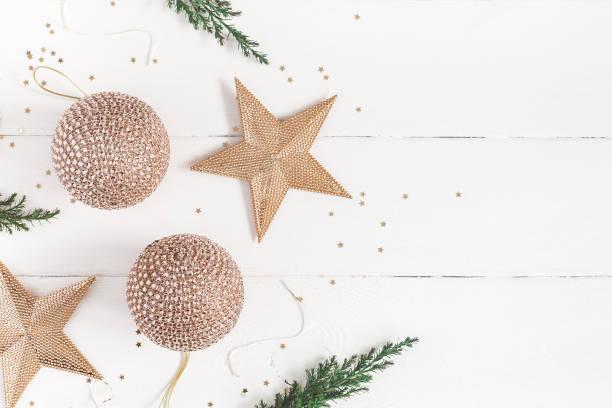 goldene weihnachtsschmuck auf weißem hintergrund aus holz. weihnachten, neujahr, winter-konzept. flach legen, top aussicht, textfreiraum - holzdeko weihnachten stock-fotos und bilder