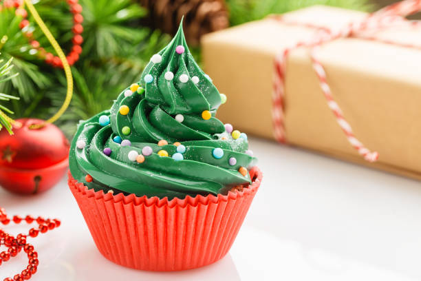 Christmas green cupcake in red cup with decorations stock photo