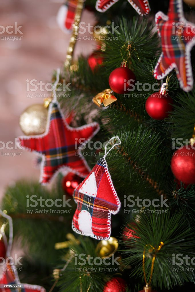 christmas green pine tree decorated with red colourful toys stars balls sox and horse in studio