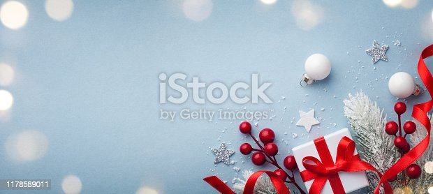 1076063742 istock photo Christmas greeting card. Fir tree branches, holiday decorations and gift or present box top view. 1178589011