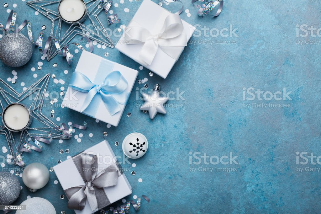 Christmas greeting card. Gift boxes, silver balls, confetti, star and sequins on blue vintage table top view. Flat lay. stock photo