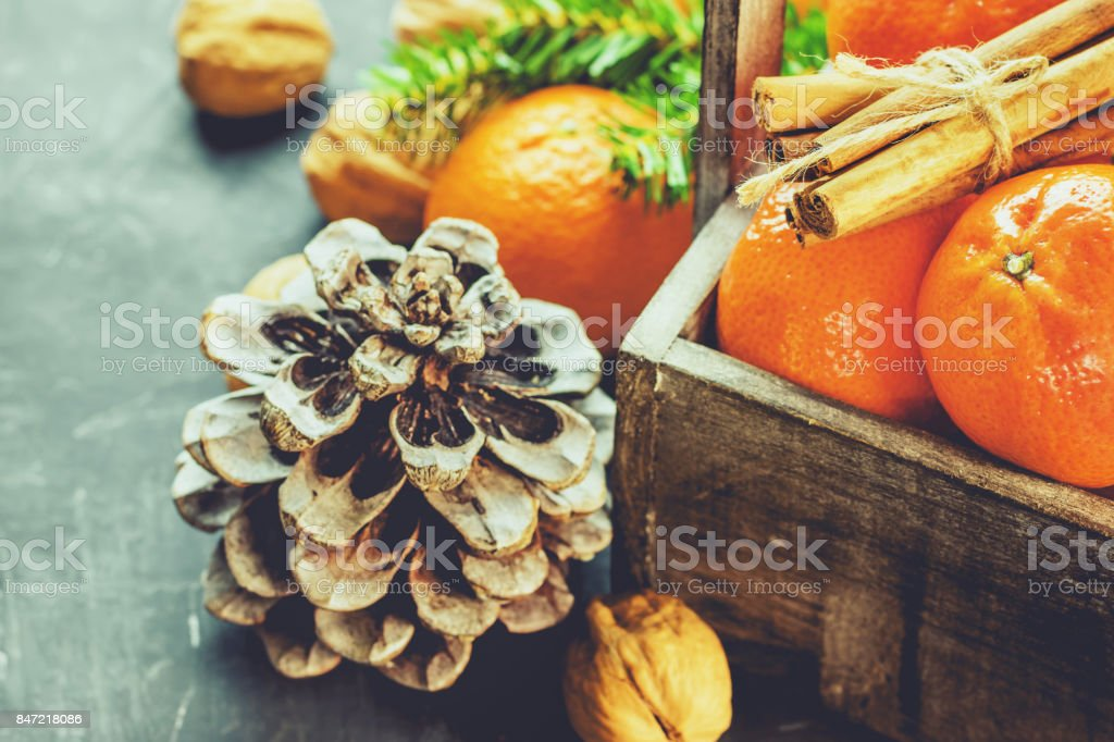 Christmas Greeting Card Tangerines Cinnamon Sticks Fir Tree Branches Pine Cones Walnuts in Wood Box Black Background New Years Poster Copy Space stock photo