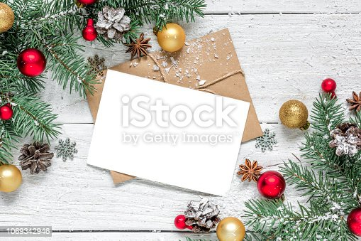 istock christmas greeting card with fir branches, star anise, decorations and pine cones on white table covered with snow 1069342946