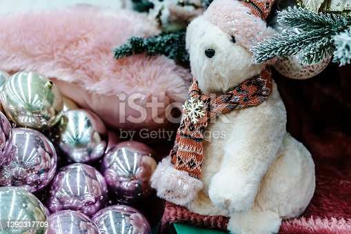 Cute teddy bear in a scarf is sitting under the Christmas tree