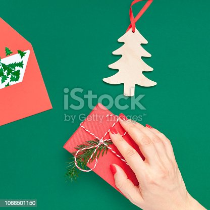 New Year or Christmas top view Xmas holiday celebration woman hand red manicure holding present gift box copy space green color paper background. Square Template greeting card