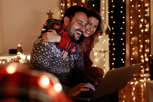 Loving couple enjoying Christmas celebration at home by themselves. Surfing and buying presents online.