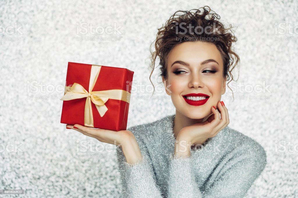 Christmas happy smiling young woman holds gift box in hands stock photo