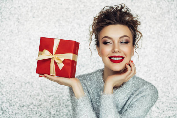 christmas happy smiling young woman holds gift box in hands - makeup fashion stock pictures, royalty-free photos & images