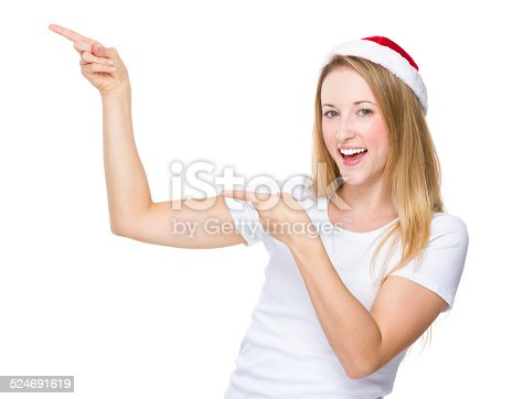 istock Christmas hat woman with finger point up 524691619