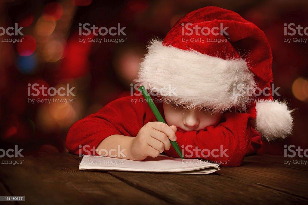 Christmas helper child writing letter in Santa hat stock photo
