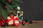 istock Christmas holiday background. Gifts with a red ribbon, Santa's hat and decor under a Christmas tree on a wooden board. 876934770