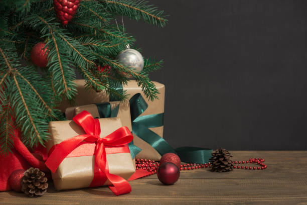 Christmas holiday background. Gifts with a red ribbon, Santa's hat and decor under a Christmas tree on a wooden board. stock photo